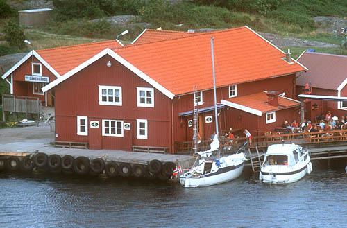 Koster museum, stor röd byggnad vid bryggan.