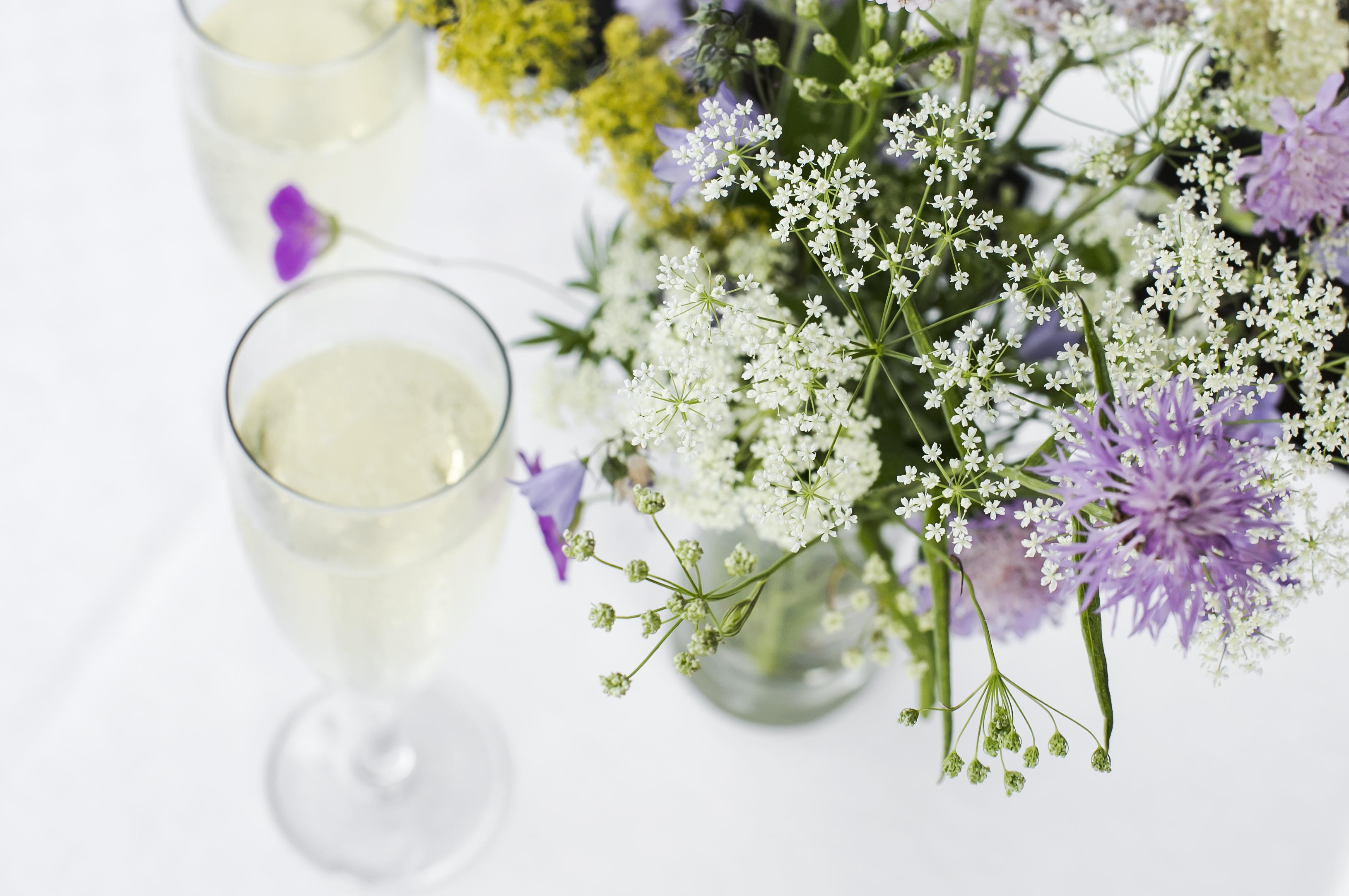 Uppdukat för bröllopsfest, skira vita blommor och glas på en vit duk