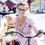 En mamma med sitt barn och mamman håler i en cykel
