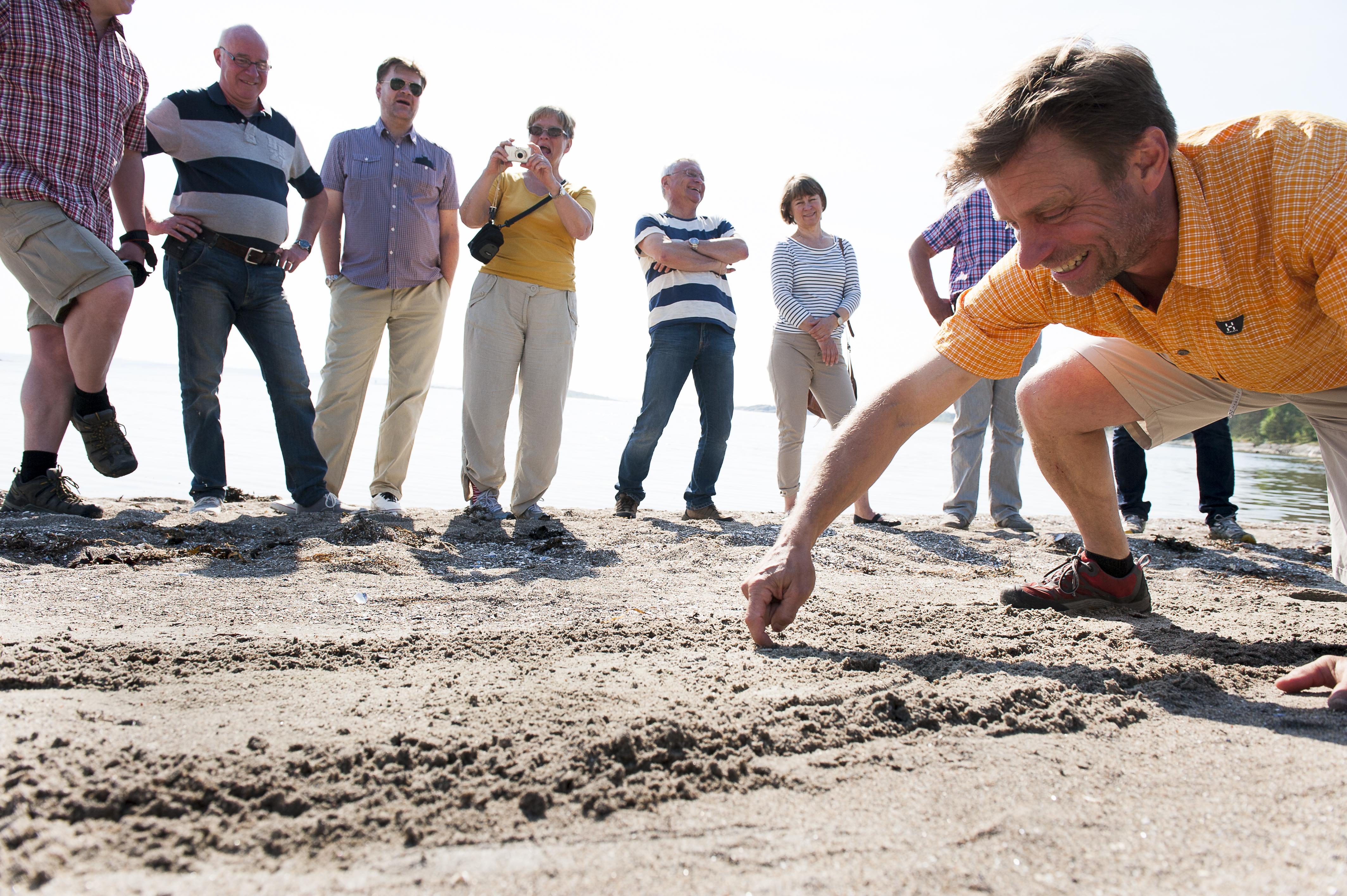 Stefan, guide på Kosteröarna ritar i sanden vid havet