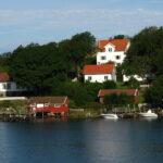 Vita sommarhus med röda sjöbodar vid havet